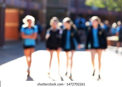 deliberate blurred shot of 4 anonymous female girl high school junior senior students walking and talking between classes lessons. education concept.