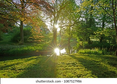 Deliberate lens flare reflected in a slow flowing stream in the Cotswold countryside, Painswick, Gloucestershire, UK