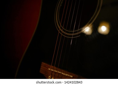 A deliberately underexposed, dark image of a black guitar. The details of the strings and smooth shape of the guitar are clearly visible. A light red glow in the background sets a romantic mood.