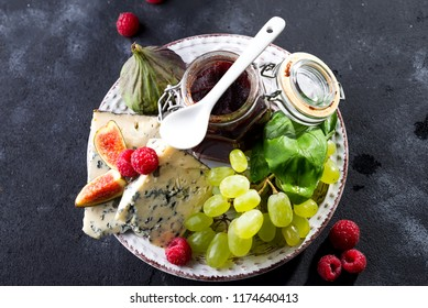 delicacy blue cheeses, fruit and jam in jar with palm leaf on dark slate stone background, copy space