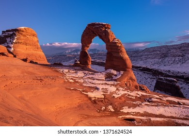 Delicate arch a national monument of Utah in rare snow covered conditions inside Arches national park outside of Moab in Utah.  The mountains of Colorado can be seen through the geological structure