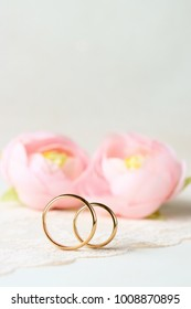 Delicate background with wedding rings and flowers.