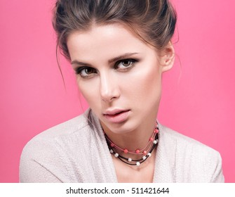 Delicate beauty closeup portrait of beautiful young woman with beads on her neck. Light makeup, hair. Pink background