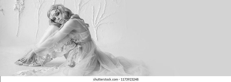Delicate black and white portrait of a young model girl. The image of the bride, a light lace dress, a beautiful hairstyle and a natural make-up. Light photo studio, natural light from the window.