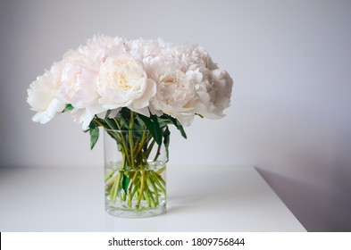 Delicate bouquet of fresh white peonies in glass vase on white table. Romantic light summer horizontal photo. Conceptual image for promotion of florist shops, schools, market, floral festivals.