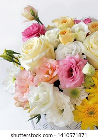 delicate bouquet of yellow roses, pink eustoma, white eustoma, white chrysanthemums, yellow chrysanthemums, green close-up on a white background with a blurred background