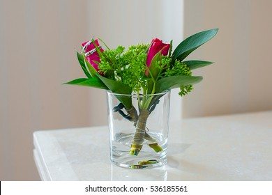 Delicate boutonniere with small roses and wedding rings