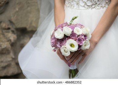Delicate bride's hands hold a wedding bouquet made of violet and white peonies