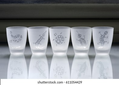 Delicate cups of liquor sandblasted with drawings of animals