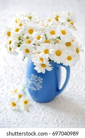 Delicate daisy flowers in a blue ceramic vase .