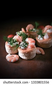 Delicate filo pastry Vol Au Vent canapes with fresh tiger prawns, soft cheese, chives, cucumber and dill garnish shot with creative lighting and generous accommodation for copy space.