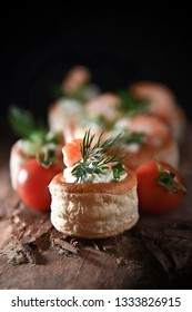 Delicate filo pastry Vol Au Vent canapes with fresh tiger prawns, soft cheese, chives, tomatoes, cucumber and dill garnish shot with creative lighting and generous accommodation for copy space.