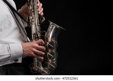 Delicate fingers of talented male musician on the silver vintage saxophone. Black background in the studio. Space for text in the right corner of the shot.