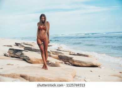 A delicate, fragile, slender girl walks along the ocean shore. The model neatly steps from foot to foot, the wind develops its long thick hair, the girl looks down.