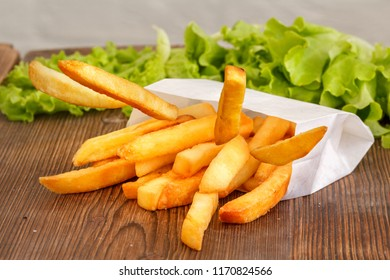 Delicate French fries on a wooden background. Close-up.