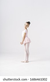 Delicate girl ballerina standing in ballet pose on white background in studio. Kinds personality development concept.