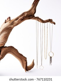 Delicate hand crafted gold and silver necklaces hanging from a twisted driftwood branch on a white background