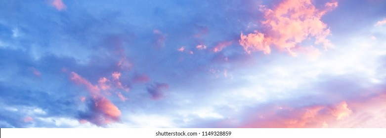 A delicate heavenly cloudscape sky with pink and white coloured cumulus cloud formation in a pastel blue sky. Sunset background image, Beauty in nature. New South Wales, Australia.