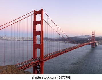 Delicate lilac, pink and purple hues play in the sky behind high-resolution stitched image of Golden Gate Bridge. Copyspace on top right.