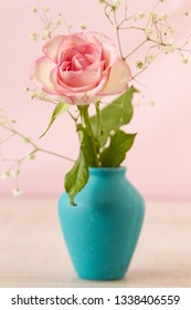 Delicate mini pink rose in a vintage blue vase on a tablein front of pink backgroud