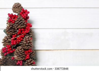 Delicate pinecone Christmas tree with red holly berries decoration