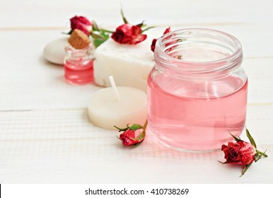 Delicate pink rose attar in jar, dried flowers, candle, relaxing aromatherapy. Soft focus, soft light.