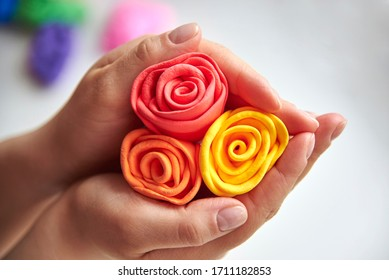 Delicate roses made of super light airy colored plasticine in the hands of a woman, developing activities.