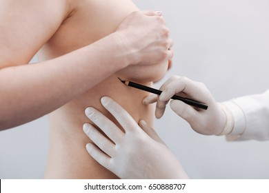 Delicate scrupulous plastic surgeon drawing special marks