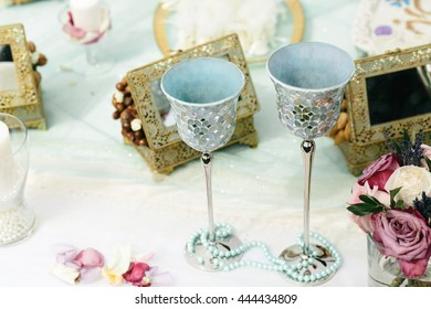 Delicate silver glasses stand behind a blue necklace on the table with decor