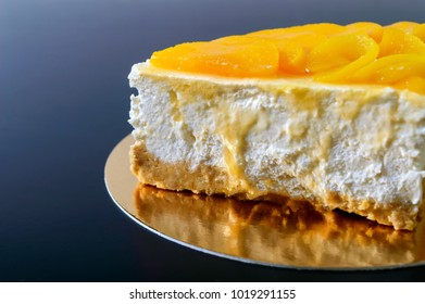Delicate souffle with juicy peaches. A large delicious piece of cake on a golden stand on a black background.