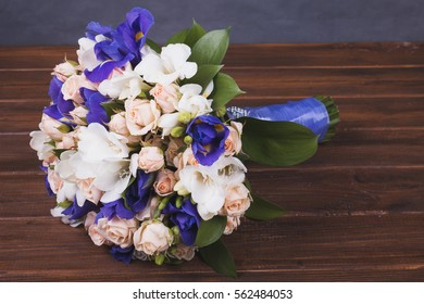 Delicate wedding bouquet of freesia and iris flowers on wooden table. Bouquet in blue colors