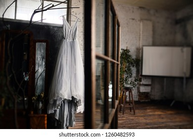 Delicate wedding dress hangs on the peg in the bright loft