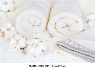 Delicate white cotton flowers and towels. Organic cotton bathroom supplies