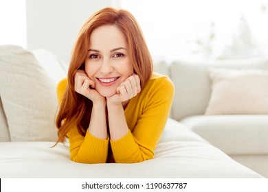 Delicate, winsome, lovable, fascinating woman with straight hair lay down on cozy couch in yellow sweater spend free time in modern white bright interior with toothy beaming smile