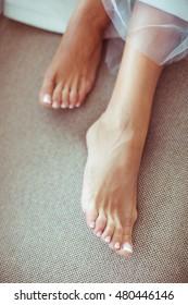 Delicate woman feet with white nail polish