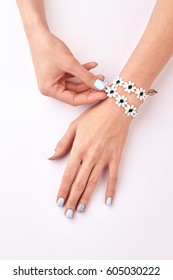 Delicate women's hands with manicure and bracelet. Blue manicure on a white background.