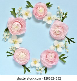 a delicate wreath of pink Ranunculus and lily of the valley on a blue background. Romantic background for wedding invitations and greeting cards. place for text. copy space. Flatlay. square format