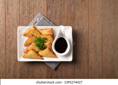 Delicios dish, Fried samosas in white plate with chocolate dipping sauce on wooden table background