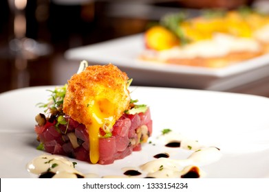 Delicious Ahi Tuna Tartare with Deep Fried Soft Boiled Egg served with sauce on a white plate