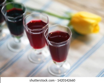 Delicious alcoholic cranberry drink in glasses on yellow rose background