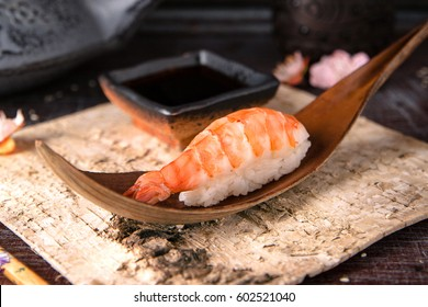 Delicious Ama Ebi Shrimp Nigiri Sushi (Shrimp Sushi) . Dish decorated with a sprig of cherry blossoms. Traditional Japanese cuisine.