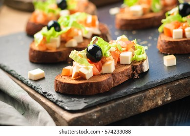 Delicious antipasti bruschetta on toasted slices of black rye bread, decorated with tomatoes, olives and greens on a black stone board, close up and selective focus