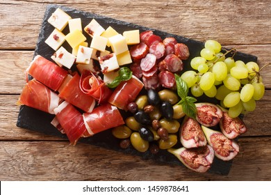 Delicious appetizer of antipasti from cheese, prosciutto ham, grapes, figs, sausages and olives close-up on a wooden table. horizontal top view from above