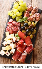 Delicious appetizer of antipasti from cheese, prosciutto ham, grapes, figs, sausages and olives close-up on a wooden table. Vertical top view from above