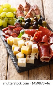 Delicious appetizer of antipasti from cheese, prosciutto ham, grapes, figs, sausages and olives close-up on a wooden table. vertical