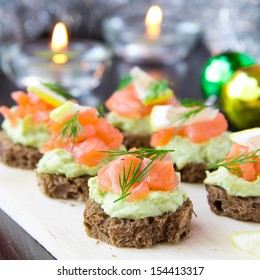 Delicious appetizer canapes of black bread, avocado and red fish salmon on board for New Year's celebratory table