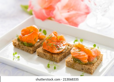 Delicious appetizer canapes of black bread with smoked salmon for holiday