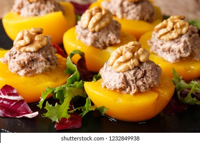 Delicious appetizer peaches stuffed with tuna and decorated with walnuts close-up on the table. horizontal