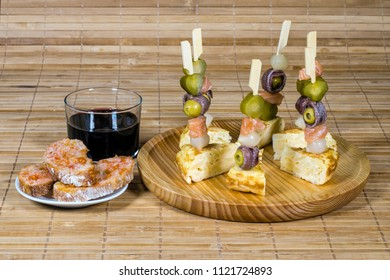 Delicious Appetizer Plate with Salmon, anchovies  and Olives. Spanish tortilla mounted. with glass red wine and bread with tomato