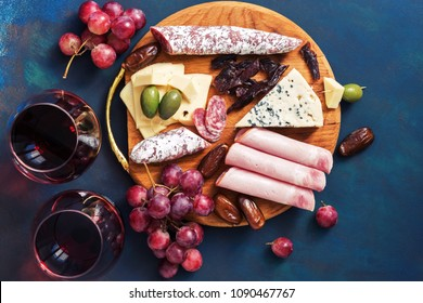 Delicious appetizers with red wine on a blue background. Fruit, cheese, ham, sausage. Top view, flat lay.